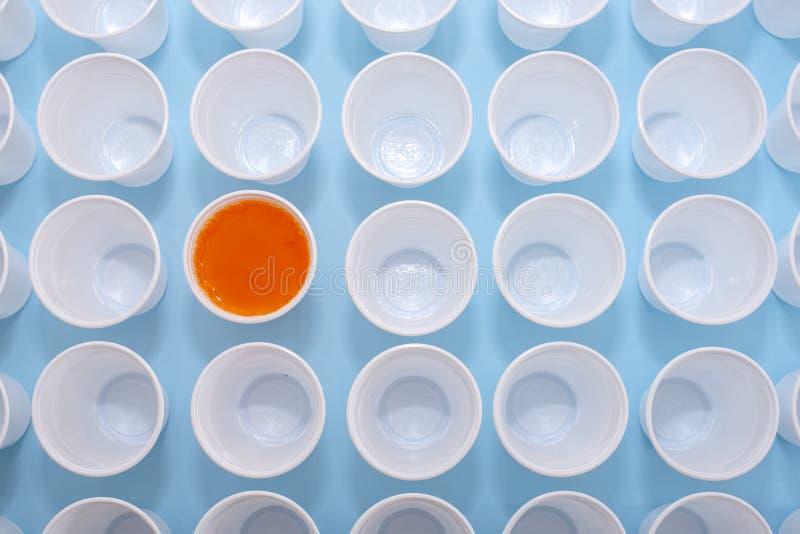 一次性塑料白色空的杯子和一块玻璃充满橙色柠檬水 库存图片