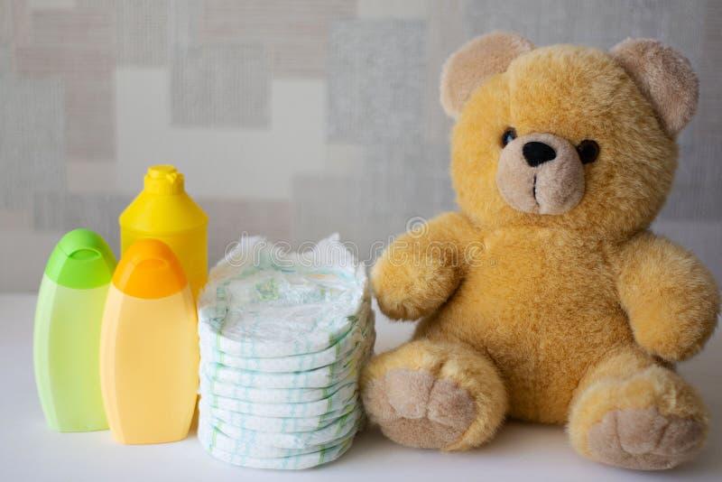 一次性尿布、婴孩辅助部件和玩具熊 免版税库存图片