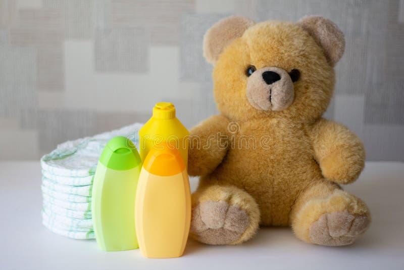 一次性尿布、婴孩辅助部件和玩具熊 库存图片