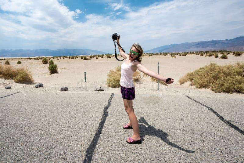 一次旅行的年轻成年女性摄影师通过死亡谷国家公园,站立并且舒展她的胳膊和腿 库存照片