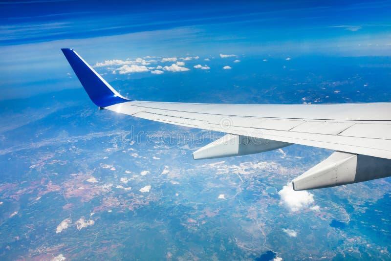 一次飞机、飞机或者飞机飞行的翼在云彩上的在天空 免版税图库摄影