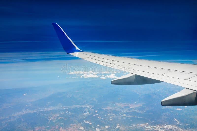 一次飞机、飞机或者飞机飞行的翼在云彩上的在天空 库存照片