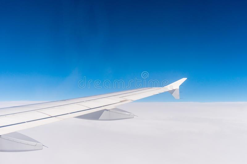 一次飞机飞行的翼在云彩之上的 天空蔚蓝的窗口视图 库存图片