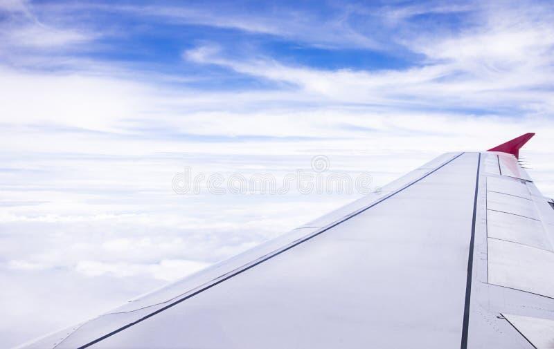 一次飞机飞行的翼在天空蔚蓝背景上的与白色云彩 图库摄影