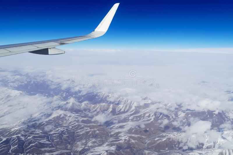 一次飞机飞行的翼在雪山上的在中国西南部 在飞机之上覆盖视图视窗 汽车城市概念都伯林映射小的旅行 免版税库存照片