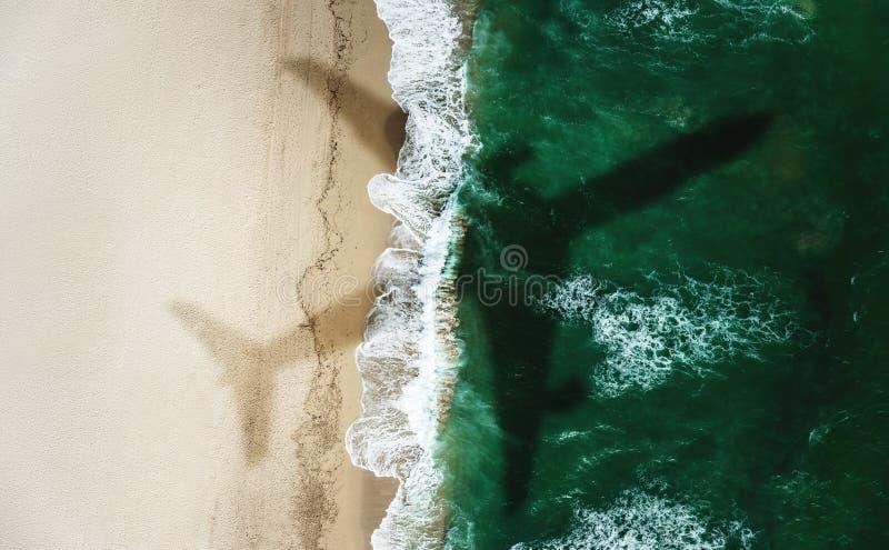 一次飞机飞行的阴影在海滩的在夏天 库存图片