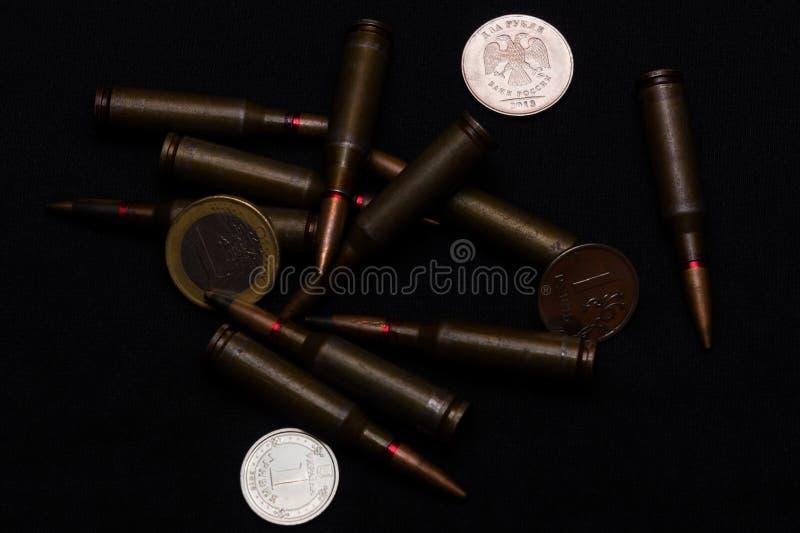 一欧元、一俄罗斯卢布和乌克兰hryvna铸造与在黑背景的步枪军用弹药 象征金钱大的战争 免版税库存图片