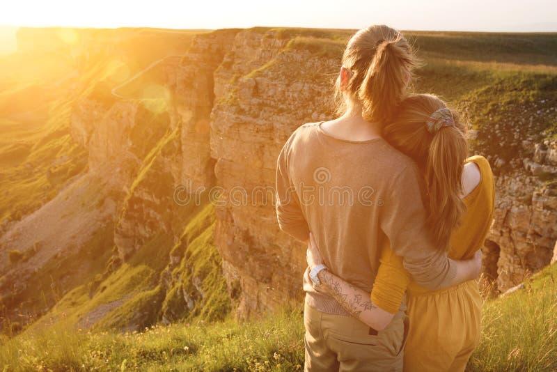 一浪漫年轻行家夫妇拥抱的后面看法画象 他们在自然上流的容忍站立在山 免版税库存照片