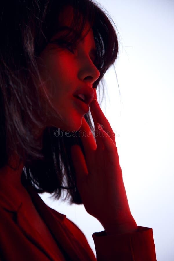 一深色的年轻女人的画象红色衣服的,摆在演播室,白色背景和红灯的在面孔 库存照片