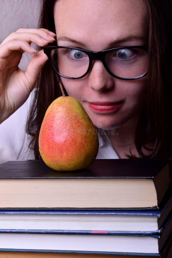 一滑稽的年轻女人戴着眼镜和凝视的画象梨 免版税库存照片