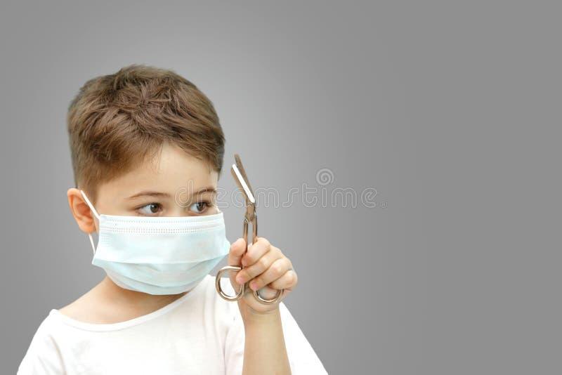 一点一个医疗面具的白种人男孩在拿着医疗剪刀的被隔绝的背景 免版税图库摄影