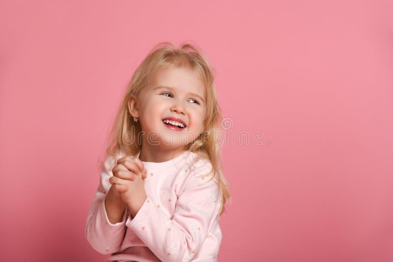 一点一套桃红色衣服的逗人喜爱的女孩儿童金发碧眼的女人是害羞的在桃红色背景 免版税库存图片