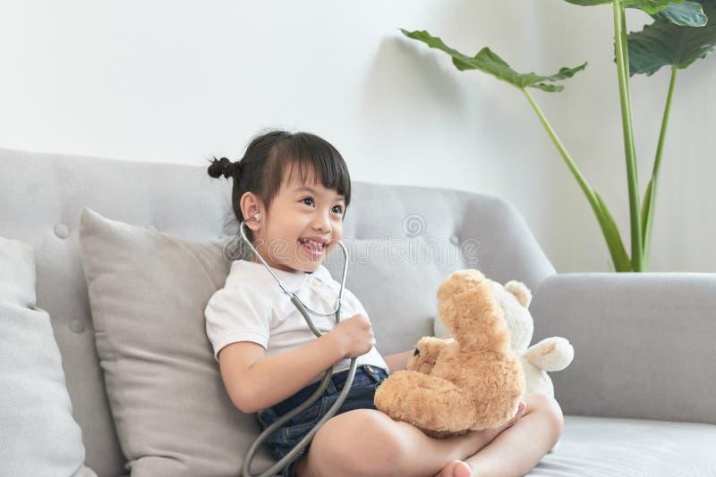 一点与娃娃玩具的亚洲女孩戏剧 小的亚洲女孩举行听诊器在手中和检查娃娃玩具 图库摄影