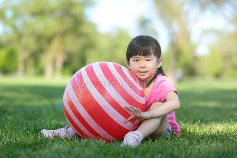 一点与红色球的亚洲女孩姿势在公园 库存图片