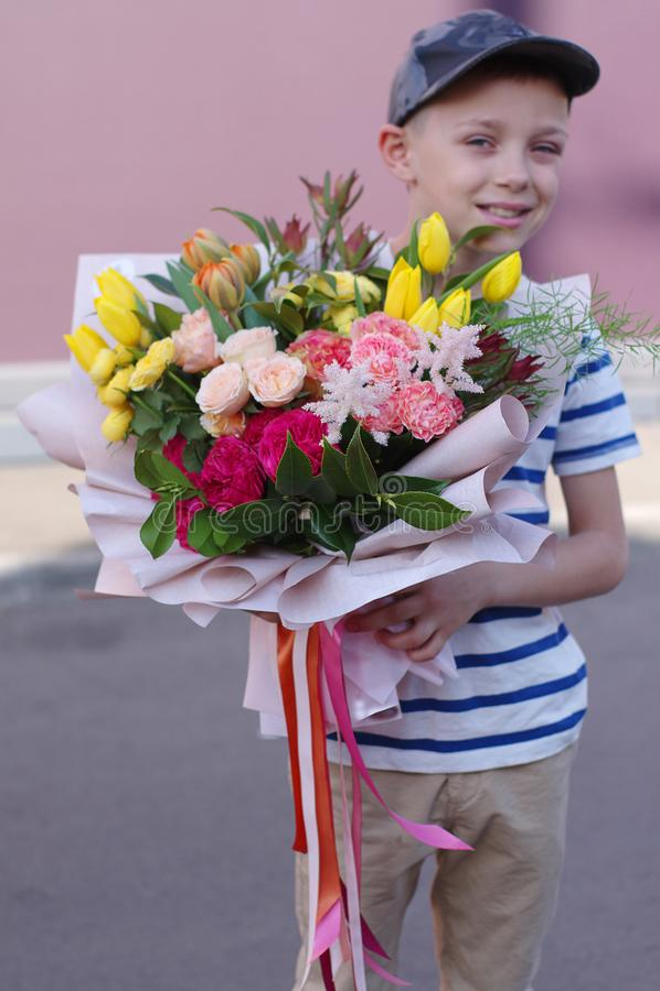 一点与花花束的微笑的男孩身分 母亲的美丽的花 库存图片