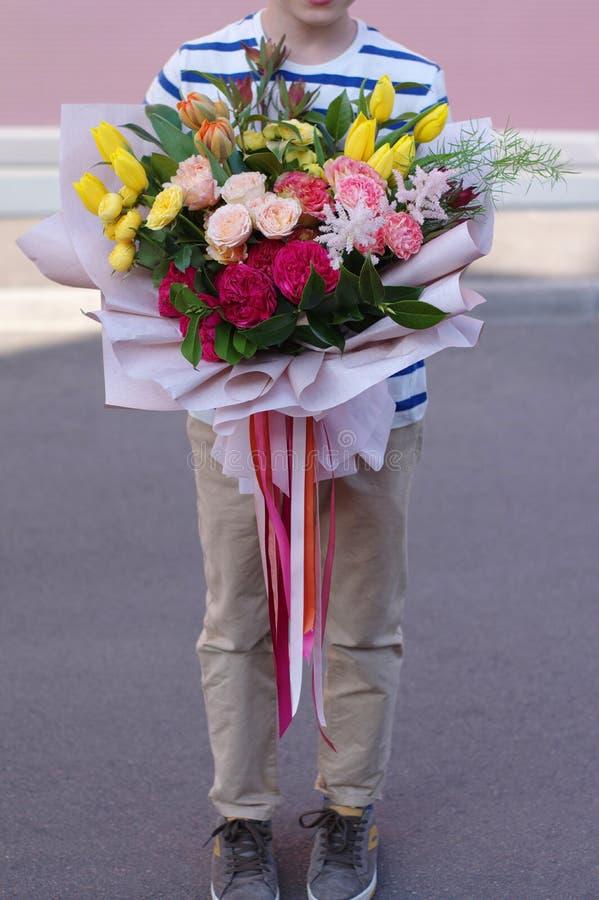 一点与花花束的微笑的男孩身分 母亲的美丽的花 免版税库存照片