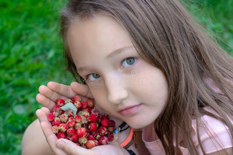 一点举行森林莓果和微笑的漂亮的孩子 有拿着新鲜的水多的森林的长发的可爱的白女孩狂放 库存图片