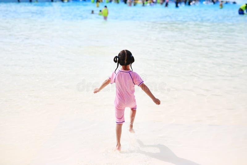 一点亚裔儿童女孩享用和赛跑入大游泳场室外在度假 获得背面图的孩子乐趣 免版税库存图片