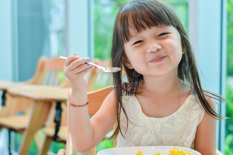 一点亚裔儿童女孩吃早餐在与一愉快的笑容的早晨 库存图片