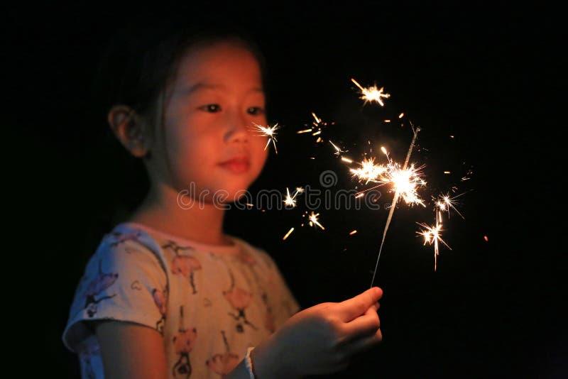 一点亚裔儿童女孩喜欢演奏爆竹 在火闪烁发光物的焦点 库存图片