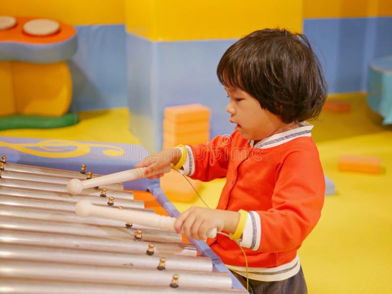一点亚裔女婴喜欢弹铁琴木琴 库存照片