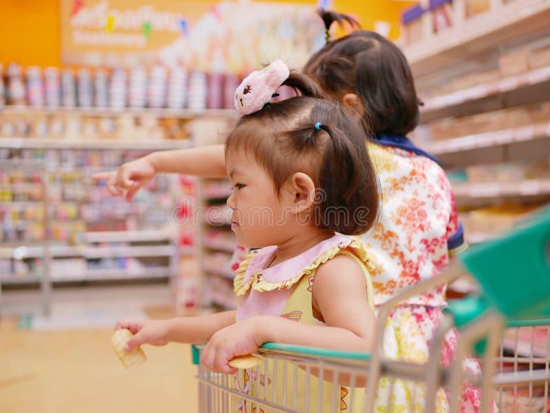 一点亚裔女婴获得站立的乐趣在有她的姐妹的一手推车,当她的母亲做购物时 免版税库存照片