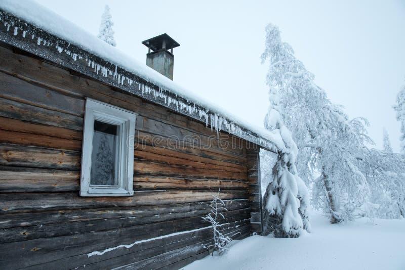 一点传统木小屋在多雪的森林里 库存照片
