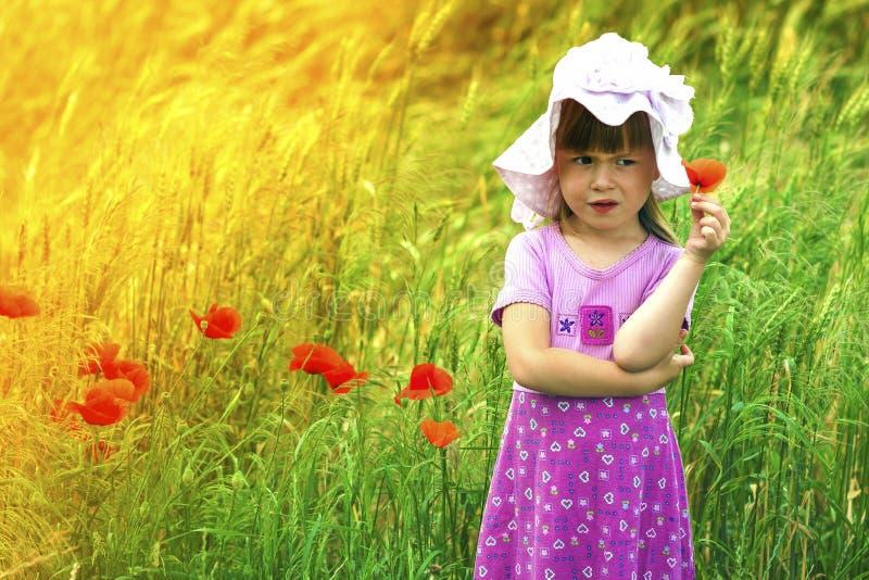 一点使并且不满意有红色花的逗人喜爱的女孩生气 免版税库存照片