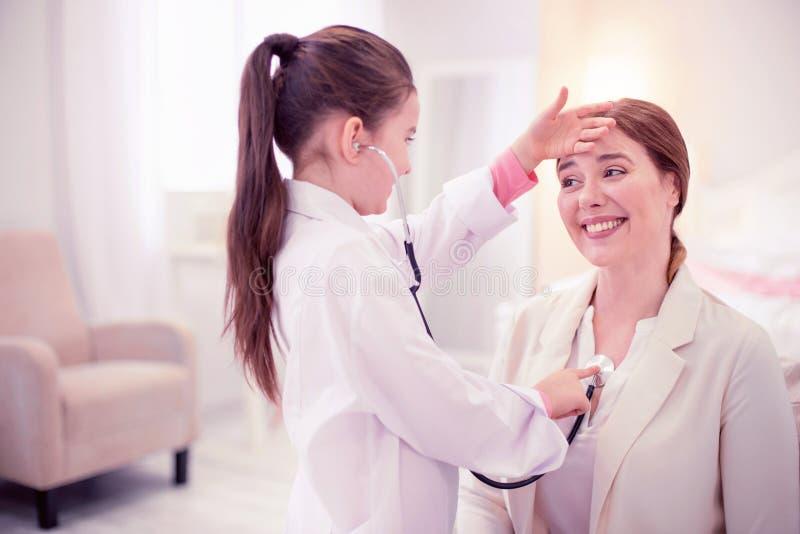一点使用与她的母亲的普通开业医生的逗人喜爱的女儿 库存照片