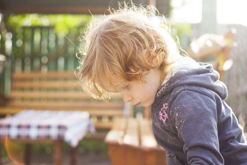 一点使用在沙盒的红发女孩在一个晴朗的夏日 免版税库存照片