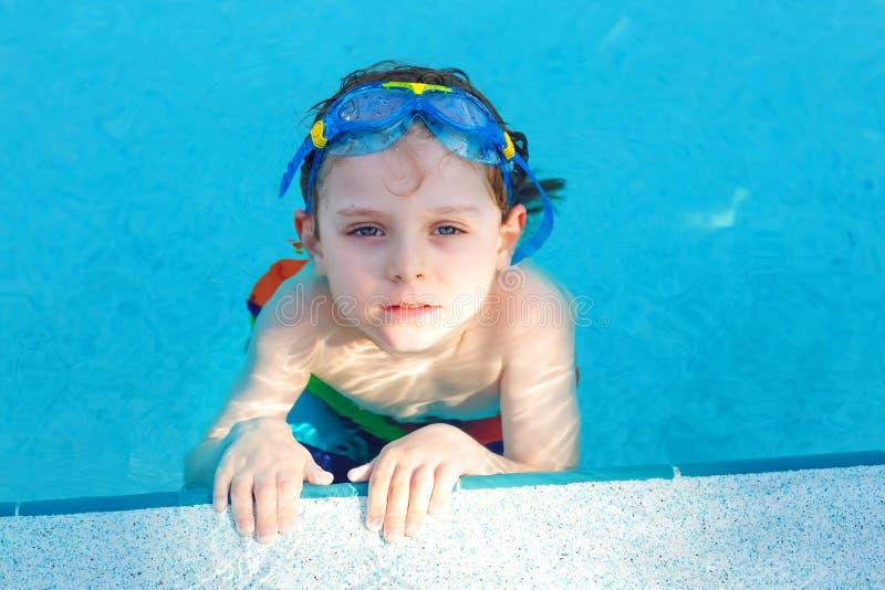 一点做游泳竞争体育的学龄前孩子男孩 与到达水池的边缘的游泳的风镜的孩子 孩子 免版税库存照片