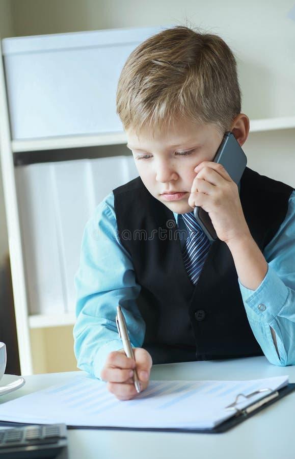 一点做笔记和谈话在电话和做笔记的行政商人上司男孩坐在书桌与 免版税图库摄影