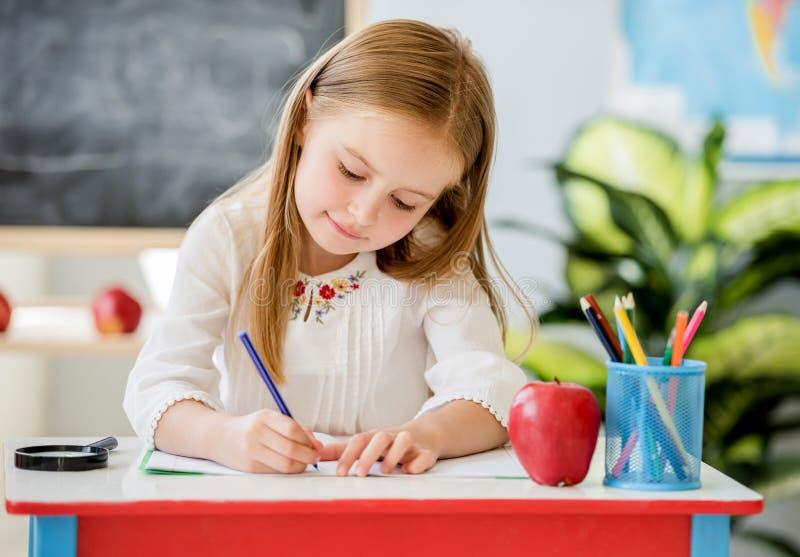 一点写功课的白肤金发的女孩在学校教室 免版税库存图片
