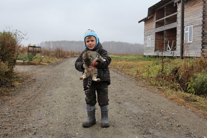 一点单独走在街道上的男婴拿着猫在秋天的房子附近 免版税库存照片