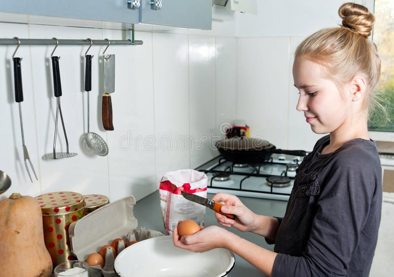 一点厨师女孩打破在一个深盘的鸡蛋 库存照片