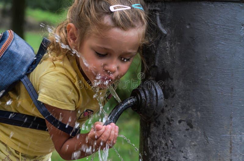 一点可爱的女孩孩子喝从饮水机'鹰鼻的'水 免版税库存图片