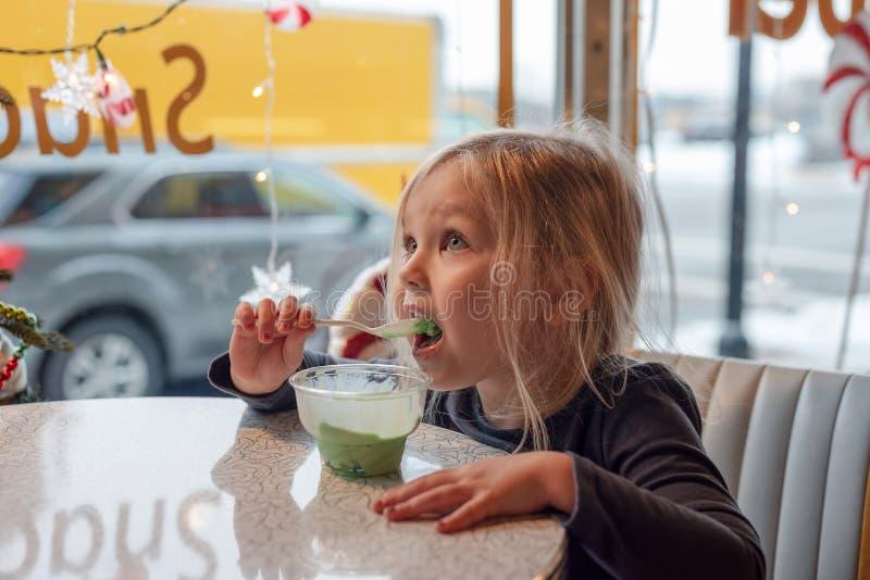 一点吃冰淇淋的白肤金发的女孩在一个减速火箭的吃饭的客人 免版税库存照片
