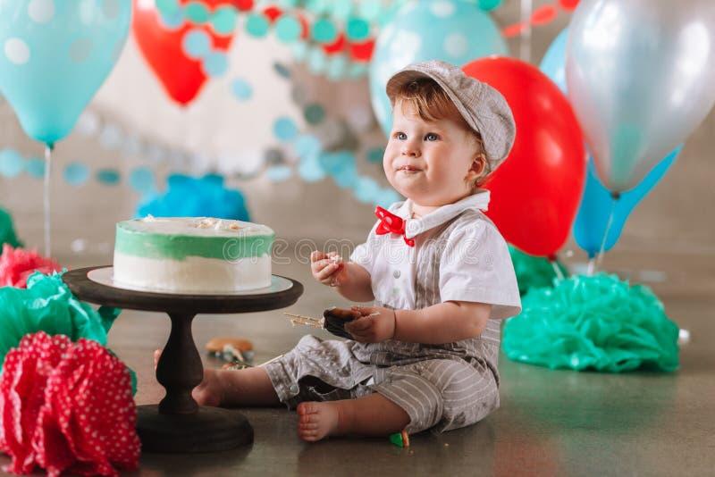 一点吃在他的第一个生日cakesmash党的男婴蛋糕 图库摄影