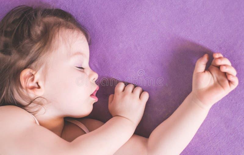 一点合理地睡觉在她的床上的可爱宝贝 库存图片