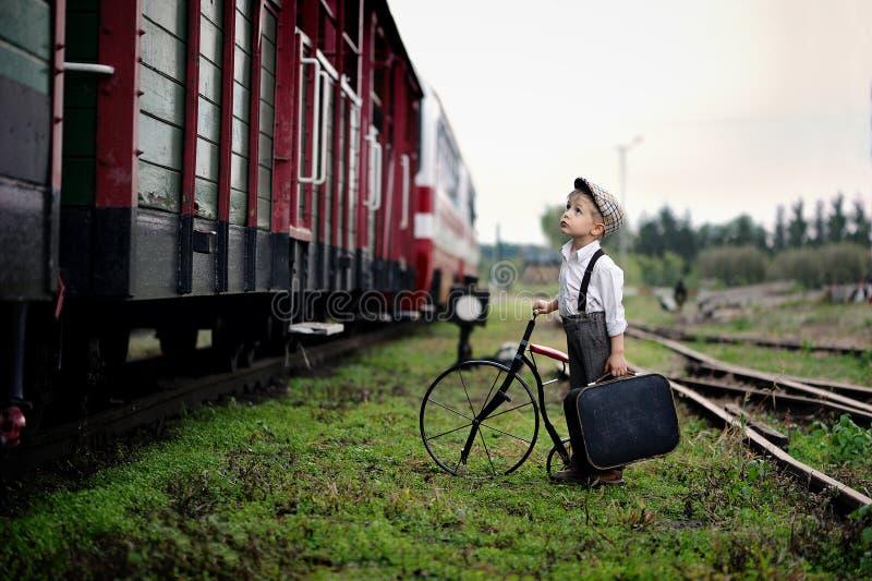 一点四岁等待火车的哀伤的男孩 免版税库存照片