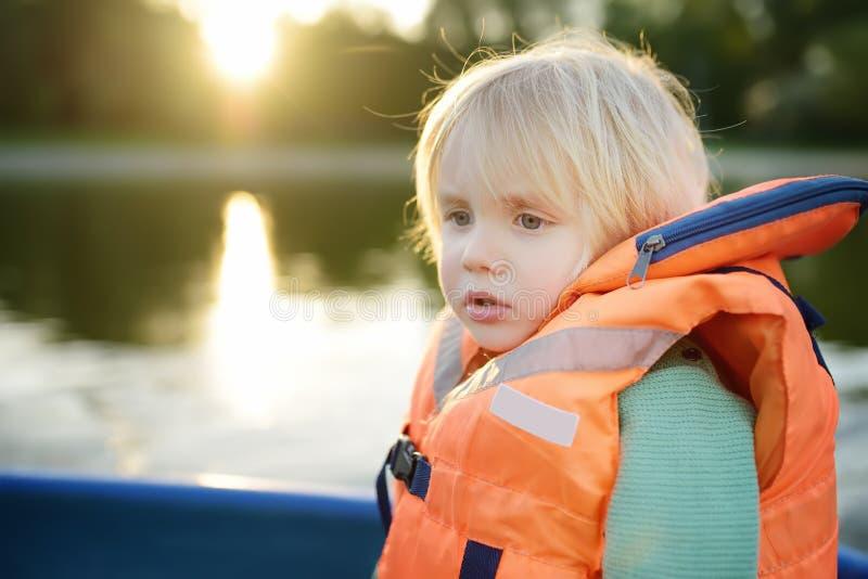 一点在一个河或池塘的害怕男孩划船晴朗的夏日 质量一起家庭时间在自然 安全性 免版税库存照片