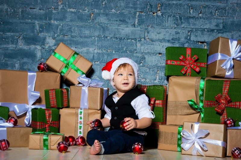 一点在圣诞节帽子和西装的微笑的婴孩圣诞老人项目 圣诞节愉快的快活的新年度 假日和礼物为 库存图片