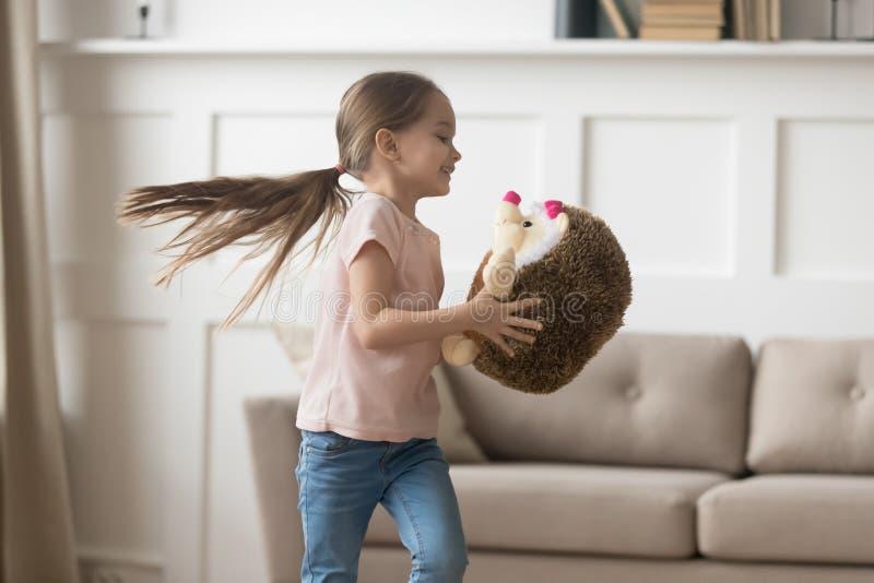 一点在家使用与被充塞的玩具猬的快乐的女孩 免版税库存照片