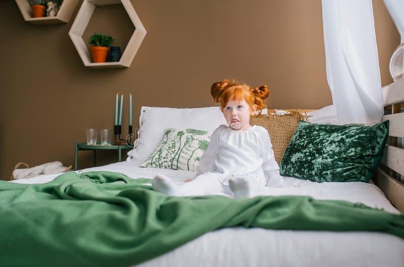 一点在家坐在床上的红头发人孩子 他有在他的面孔的一副滑稽的鬼脸 免版税库存照片