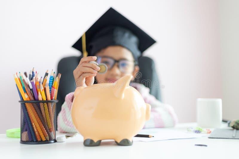 一点在将来放硬币的亚裔女孩入存钱罐和微笑充满幸福节约金钱的对wealthness  免版税图库摄影