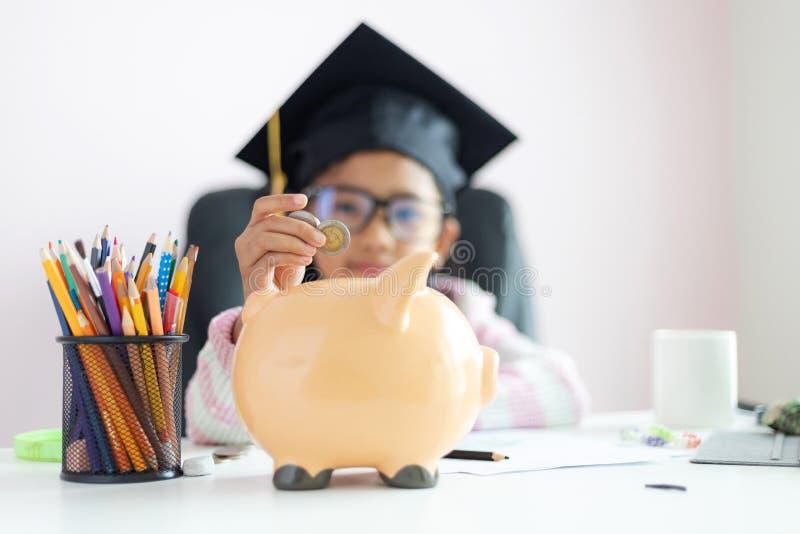 一点在将来放硬币的亚裔女孩入存钱罐和微笑充满幸福节约金钱的对wealthness  免版税库存照片