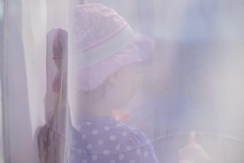 一点在看在晴朗的天气的窗口外面的帷幕后的小孩女孩,国内哀伤的孤独的虐待儿童的家庭 库存照片