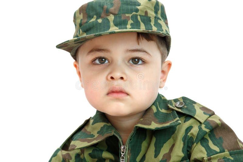 一点在轻的背景隔绝的军用衣裳的白种人男孩 免版税库存图片