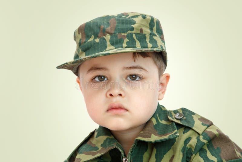 一点在轻的背景隔绝的军用衣裳的白种人男孩 库存照片