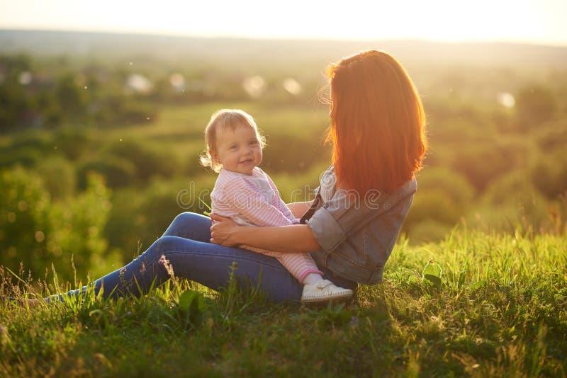 一点女儿微笑,坐母亲` s膝盖,当日落时 库存图片